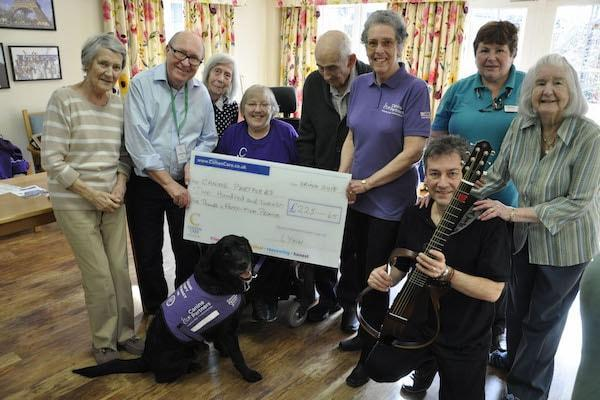 Mungo at Colten Care's Linden House care home in Lymington with his partner Barbara Houston, seated. Also joining residents and team members are Canine Partners volunteer Liz Downs, standing third from right, and singer and guitarist Nigel Revill