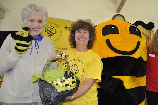 Betty Hampton, left, a resident at Colten Care's Woodpeckers home in Brockenhurst, New Forest, with items she knitted in aid of the Honeypot Children's Charity. Joining her is Viv Carter, Honeypot's Regional Community Fundraising Officer, and mascot Bumble.