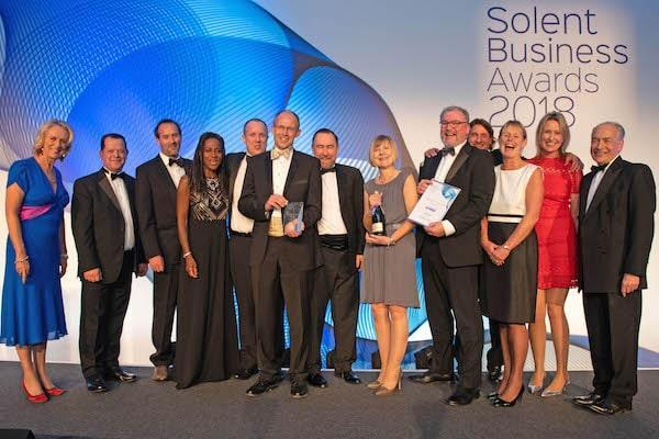 Colten Care representatives on stage at the Solent Business Awards. Hoping the trophy for Company of the Year is Mark Aitchison, Chief Executive. On the left is BBC presenter Sally Taylor and on the right is ITV's Alastair Stewart.