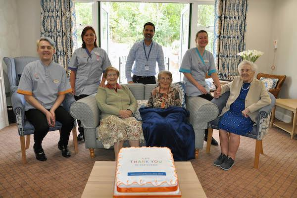 Colten Care residents present their nurses with a huge cake to mark International Nurses Day 2019.