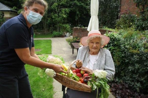 resident and nurse with basket of produce