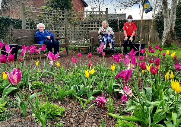 seated residents in garden full of flowers