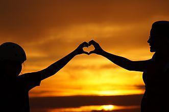 two people making a heart with outstretched arms