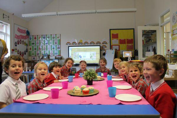 schoolchildren around table with cake