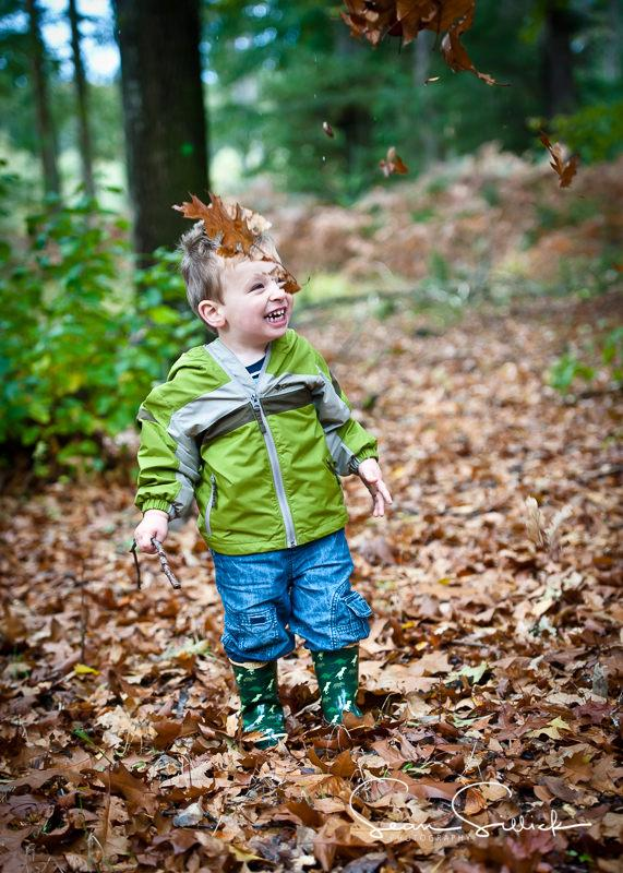 Boy playing in the autumn leaves in The New Forest